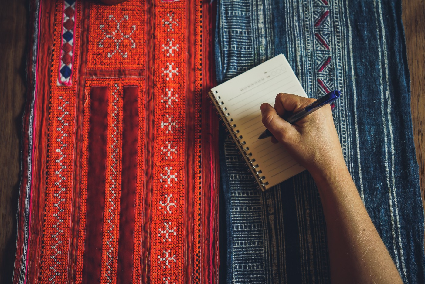 A man's hand holding a pen, about to write in a small notebook that's resting on red and blue woven & embroidered fabric