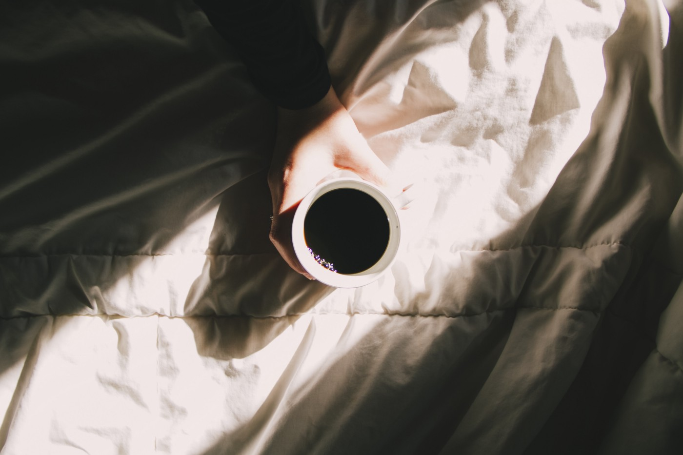 An above photo of a cup of black coffee on top of a cloth material being held by a hand coming into the frame