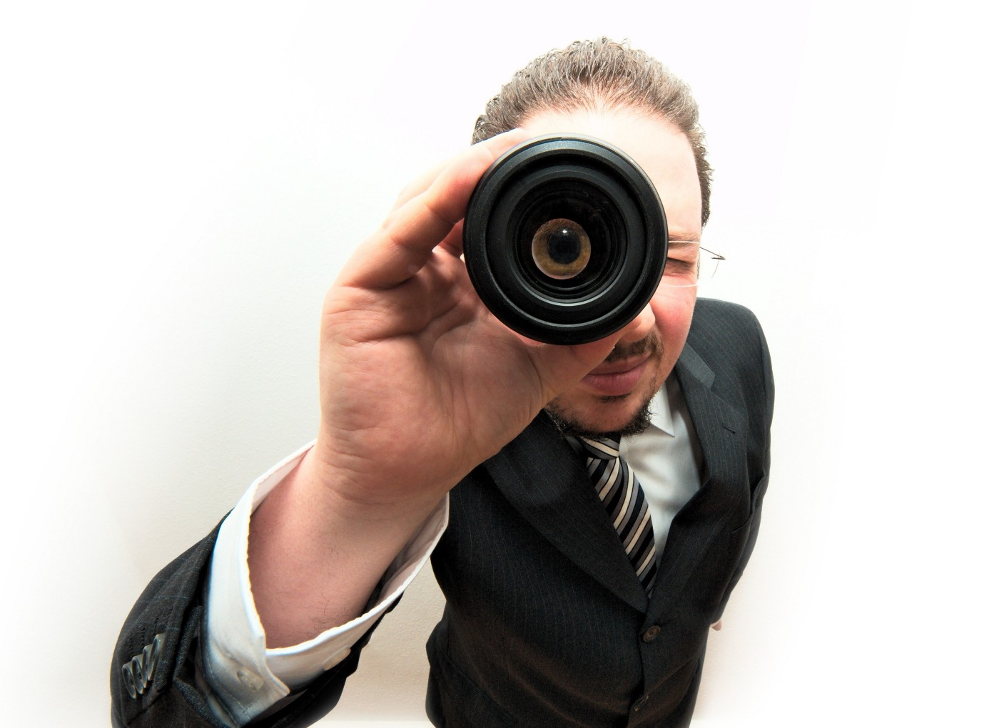 A man looking through a magnifying glass.