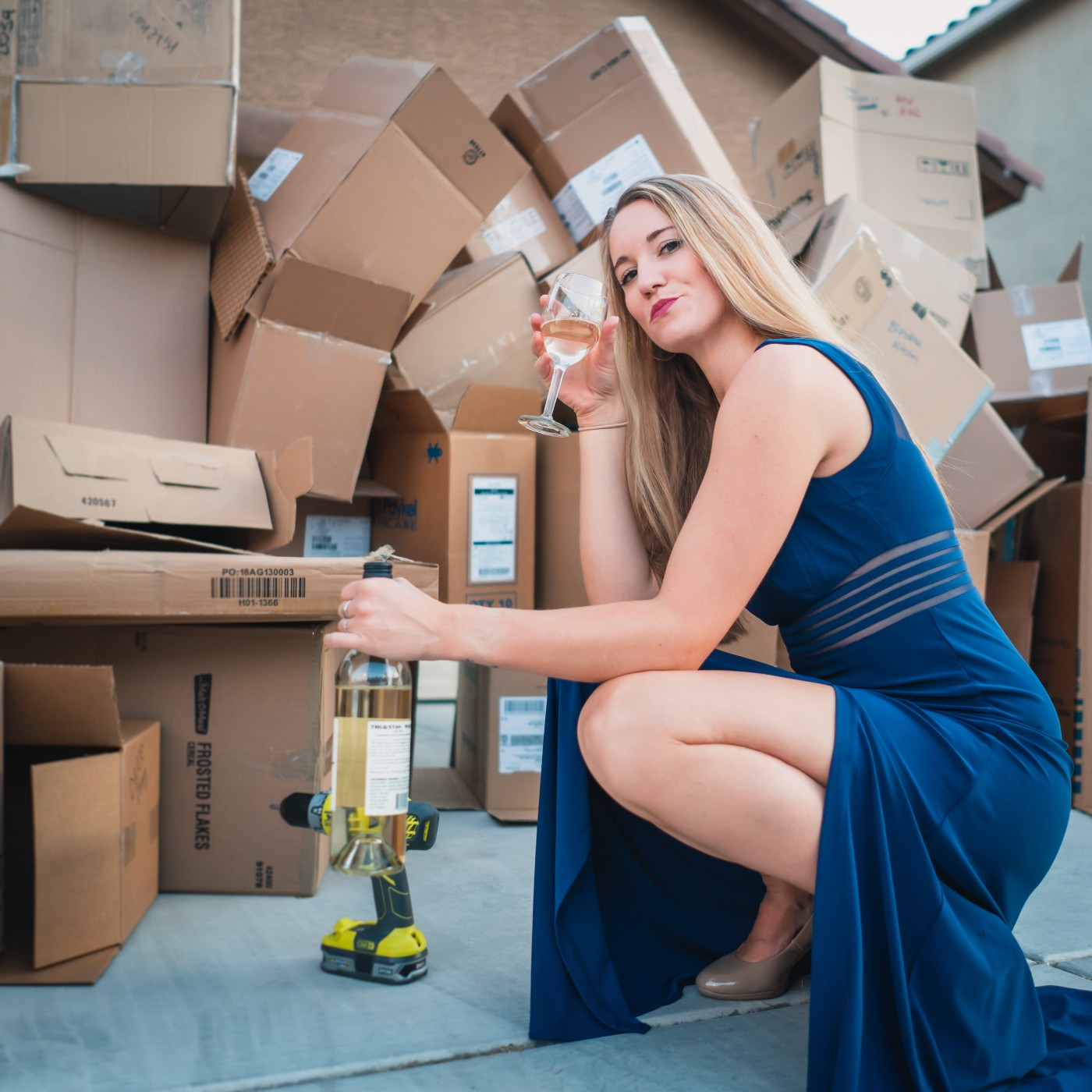 Young Woman in denim dress stoops amidst her packing boxes waitin to unpack