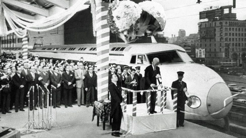 A group of Japanese officials, guards, and scientists who are standing beside the first Shinkansen train series in celebration of its opening.