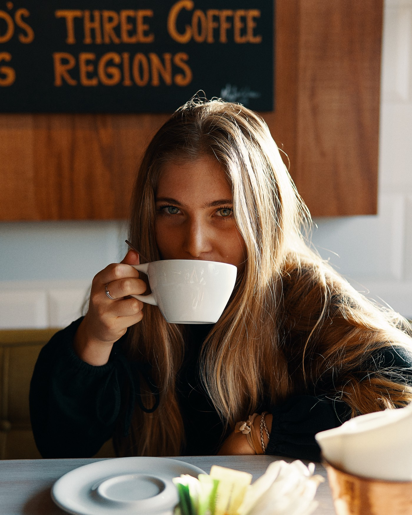 An everyday woman drinks from her mug of coffee