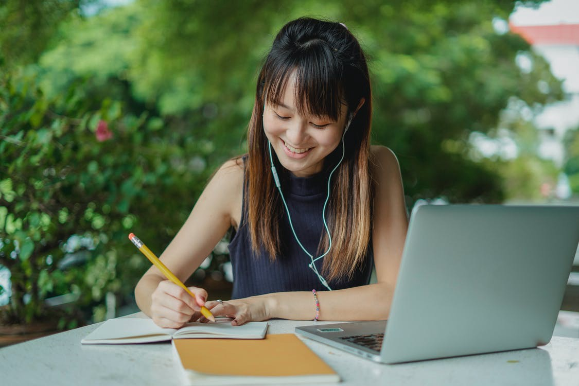 An Asian woman is smiling while writing in a notebook and listening to music using headphones. Her laptop sits in front of her. #freelancewriting #freelancing #writing