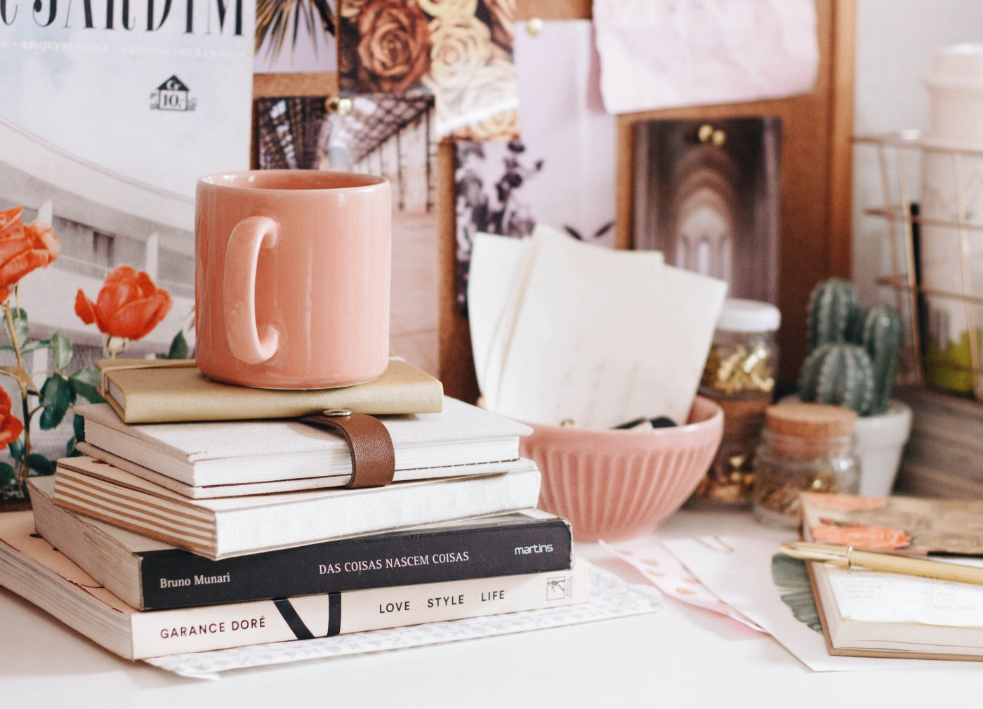 A cluttered, cosy desk space with a stack of novels and notebooks, and a pale pink mug on top.