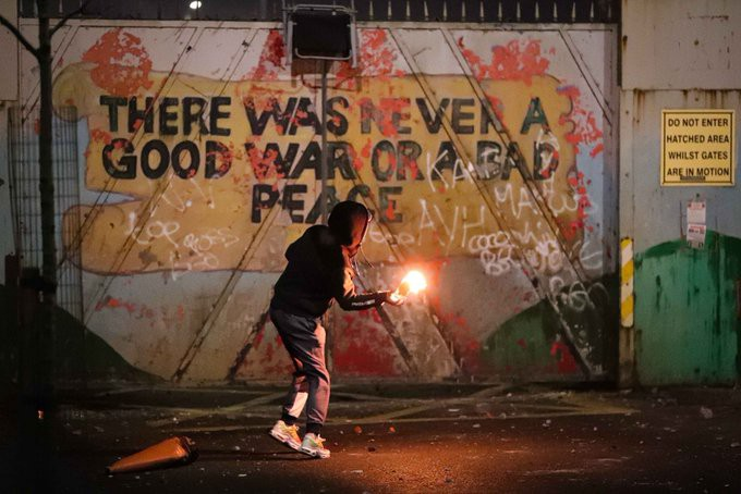 As a young person prepares to throw a petrol bomb over the interface, the words 'there was never a good war or a bad peace' stand out in bold