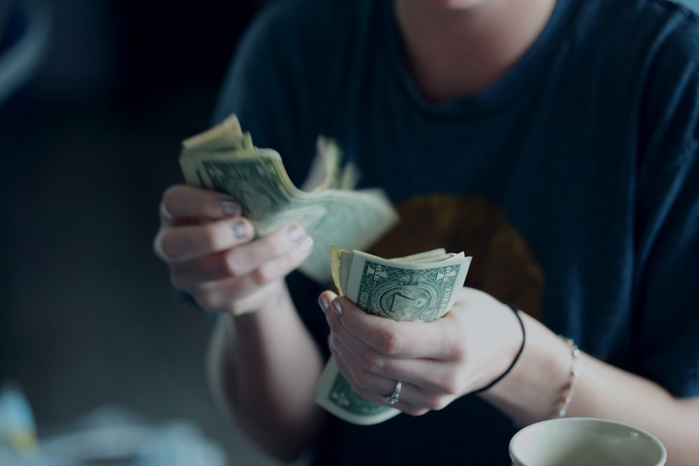 Person counting through a stack of dollar bills