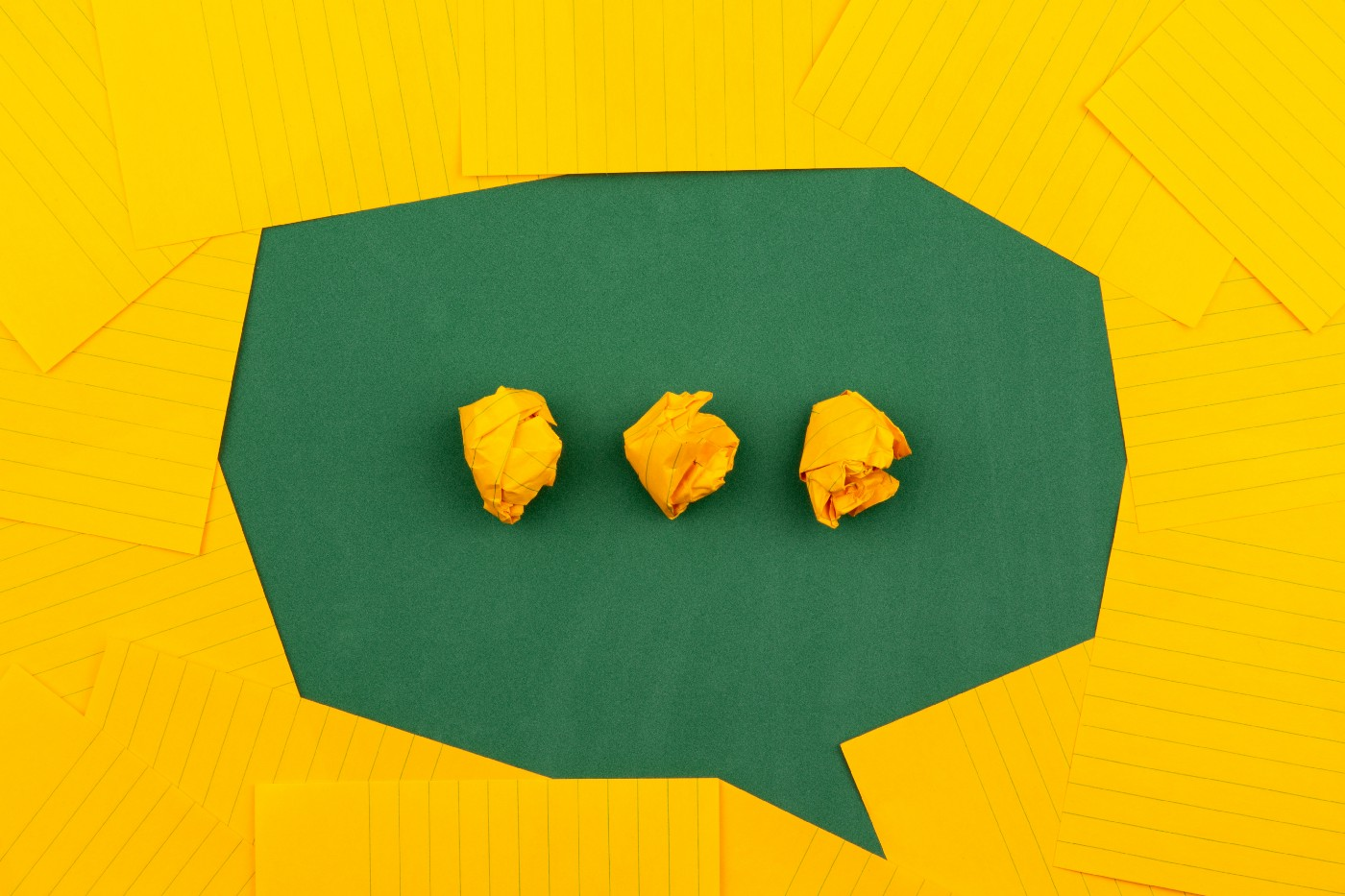 Speech bubble with three balled-up pieces of paper in it.