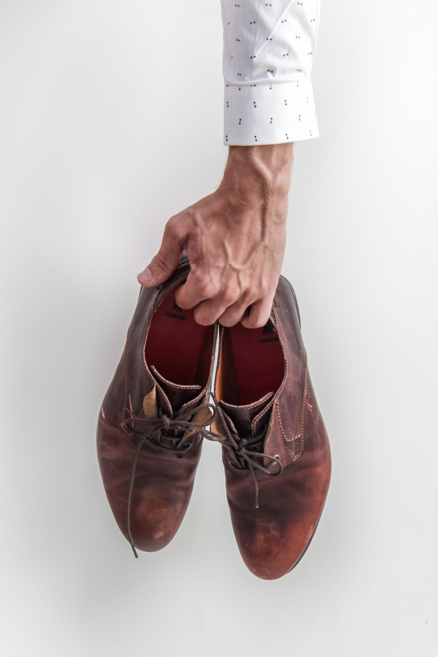 A hand holding a pair of brown shoes
