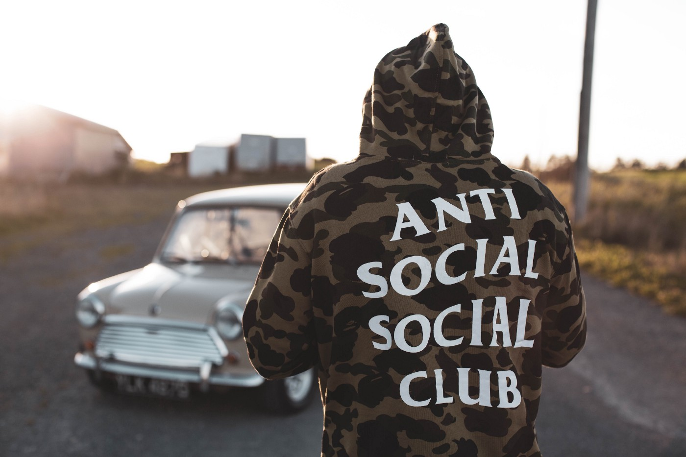 Man wearing hoodie that says anti social social club, standing in front of a car