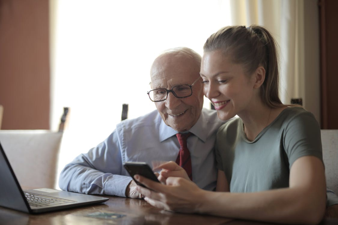 A young woman showing an elderly gentleman how to use a smartphone