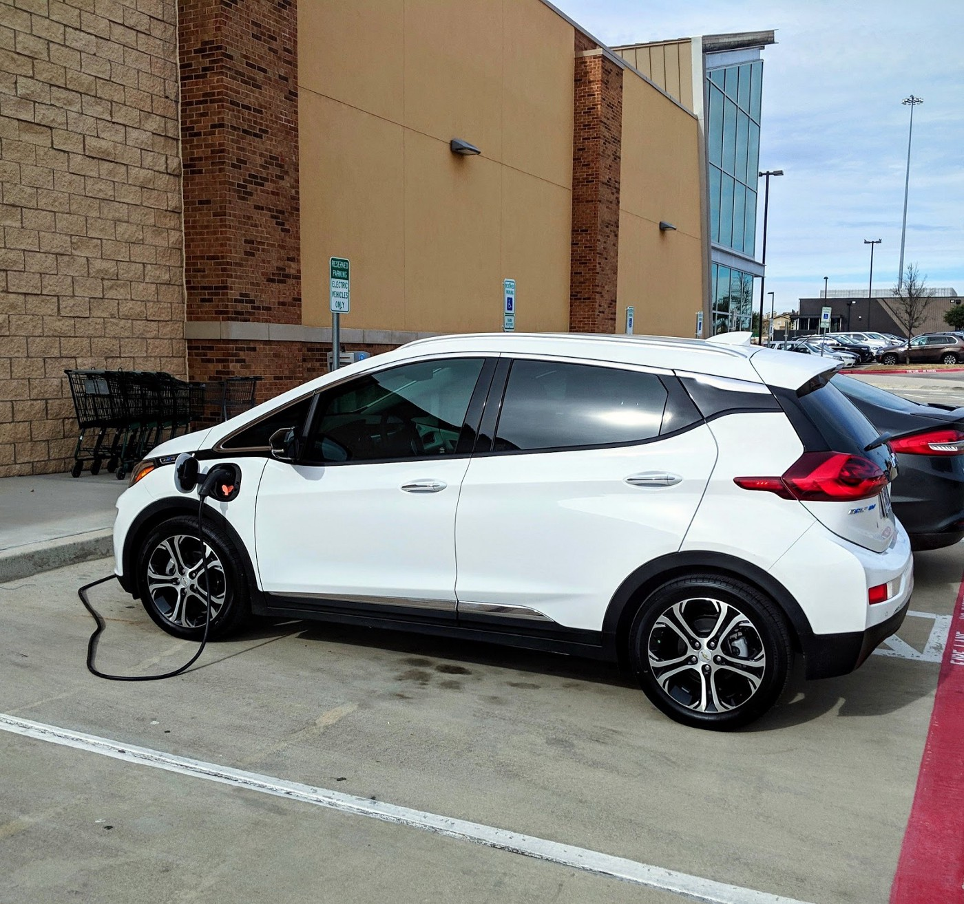 A white Chevy Bolt is being charged by an electric vehicle charger.