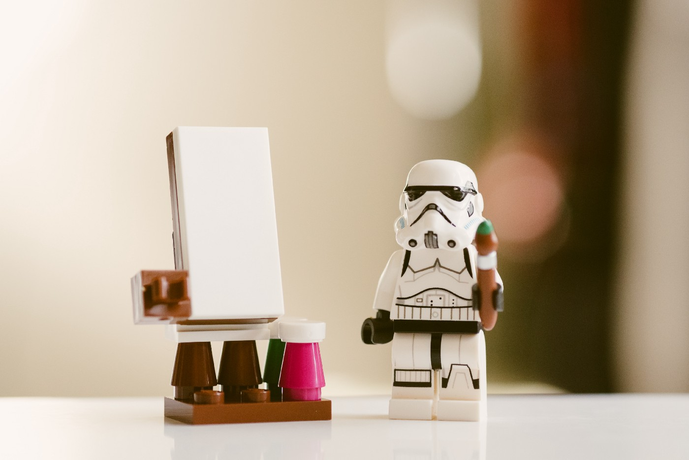 A Lego Star Wars character holding a paint brush and standing at an easel.