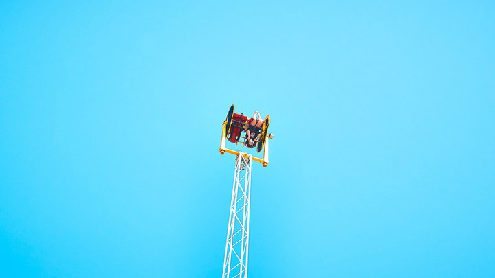 A person on a two-seater carnival ride that flings people upside down, which it is currently doing in front of a cloudless blue sky.