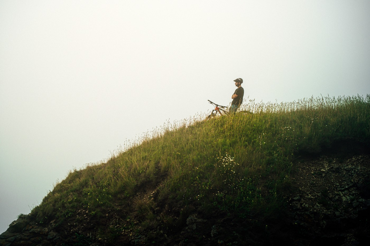 a person on a bike at the top of a hill, looking out into the fog