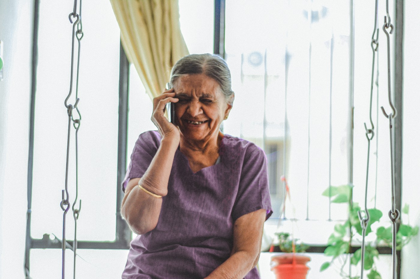A grandmother smiles and laughs as she talks on the phone.