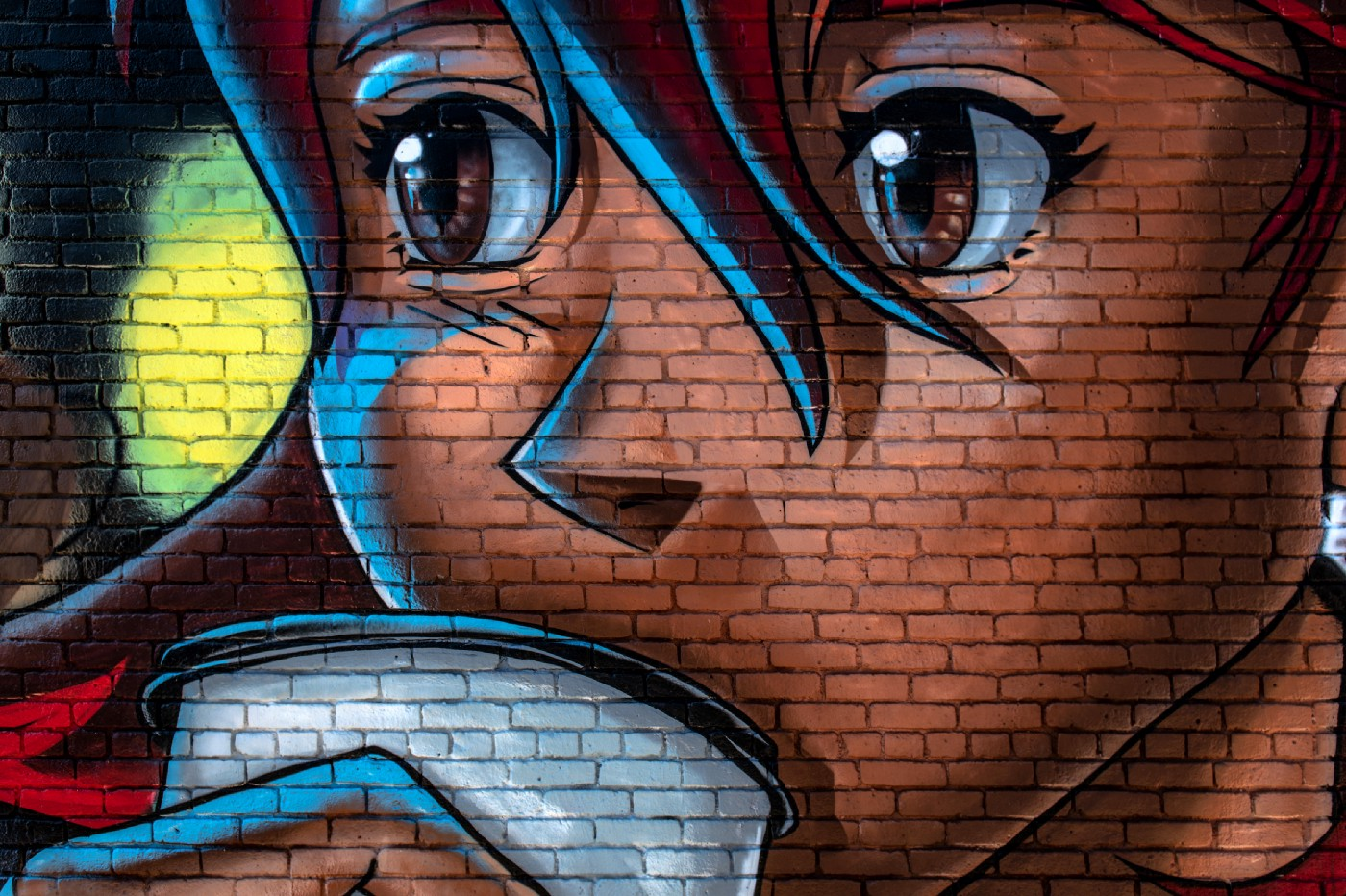 Drawing on a brick wall of an anime girl sipping coffee