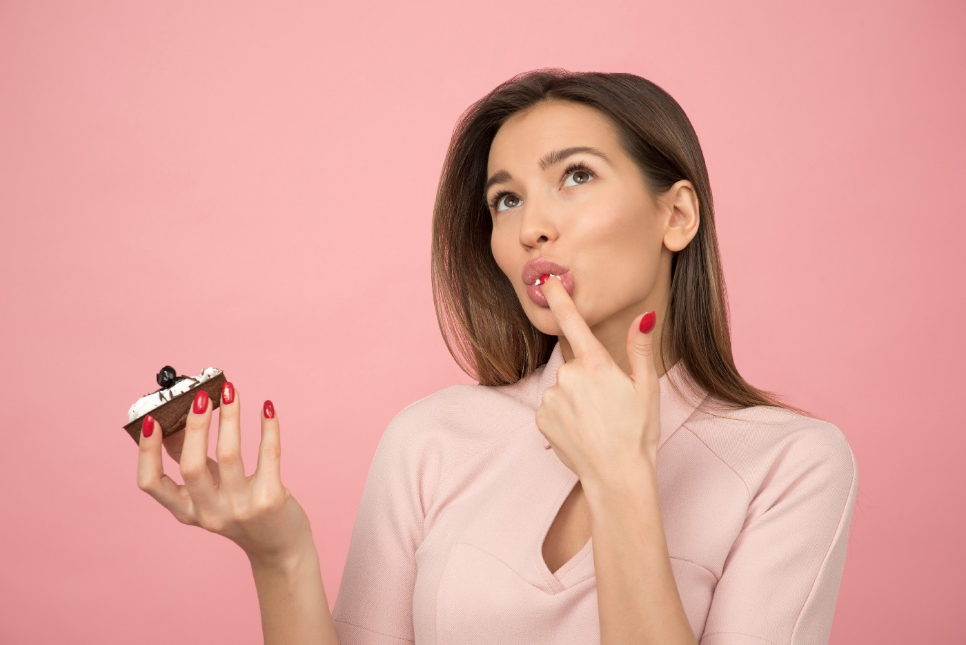 a woman holding a cupcake in one hand, her other hand has a finger in her mouth from tasting the frosting and she is looking up signaling enjoyment and thinking