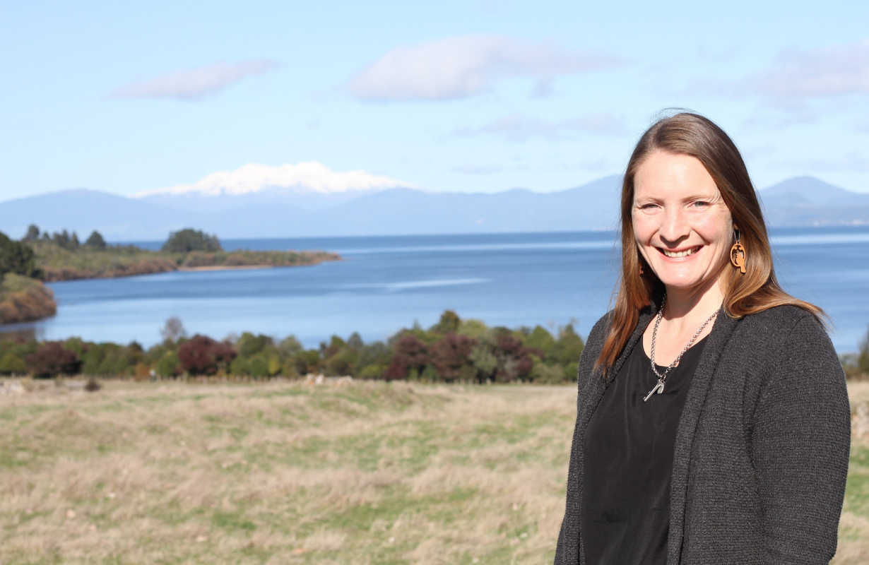 Alana to side of photo smiling at camera with field, moana (sea) and maunga (mountain) behind.