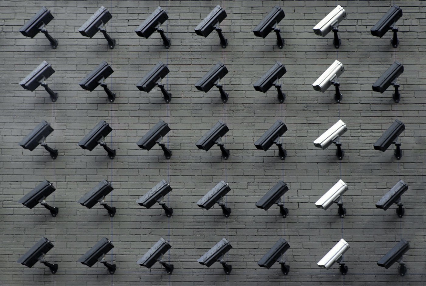 A brick wall is filled with rows and rows of security cameras.