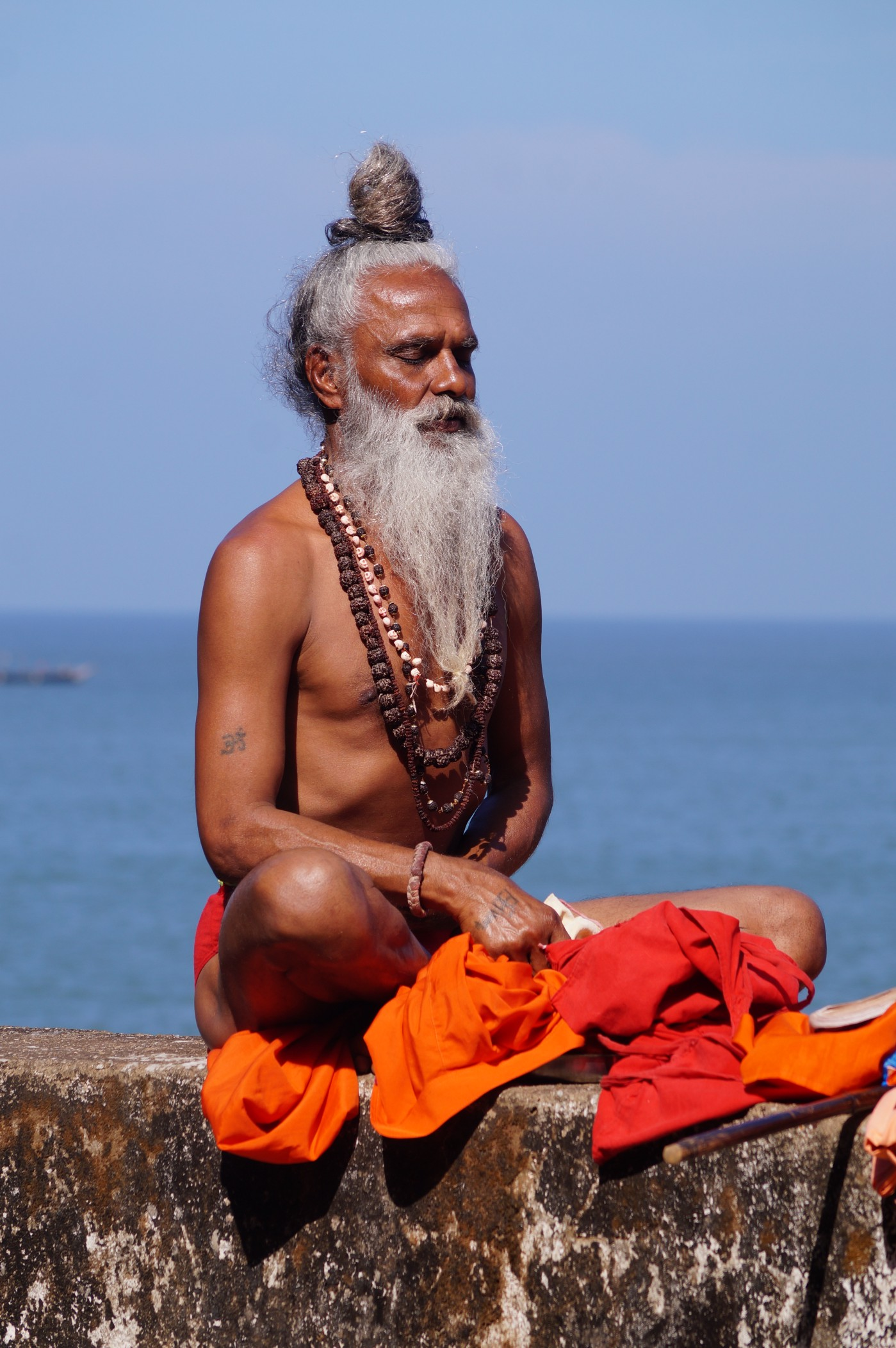 The image is of an indian yogi meditating on a wall near the sea shore.