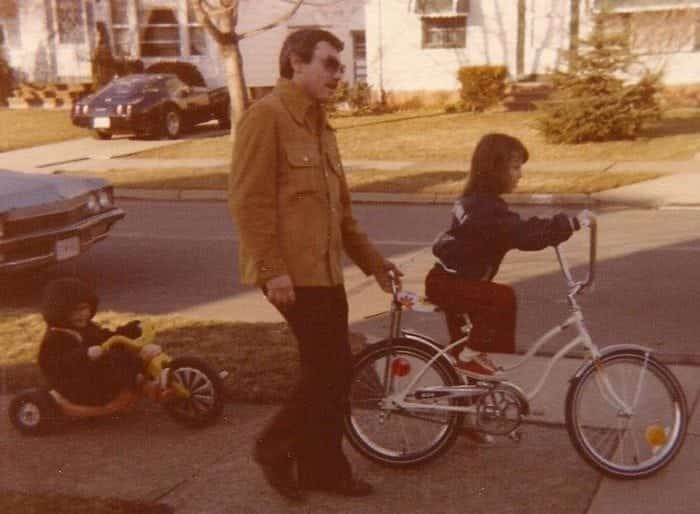 Photo showing Lou Fioritto walking alongside his daughter Christine as she's learning to ride a bike. Lou's son Ken is behind