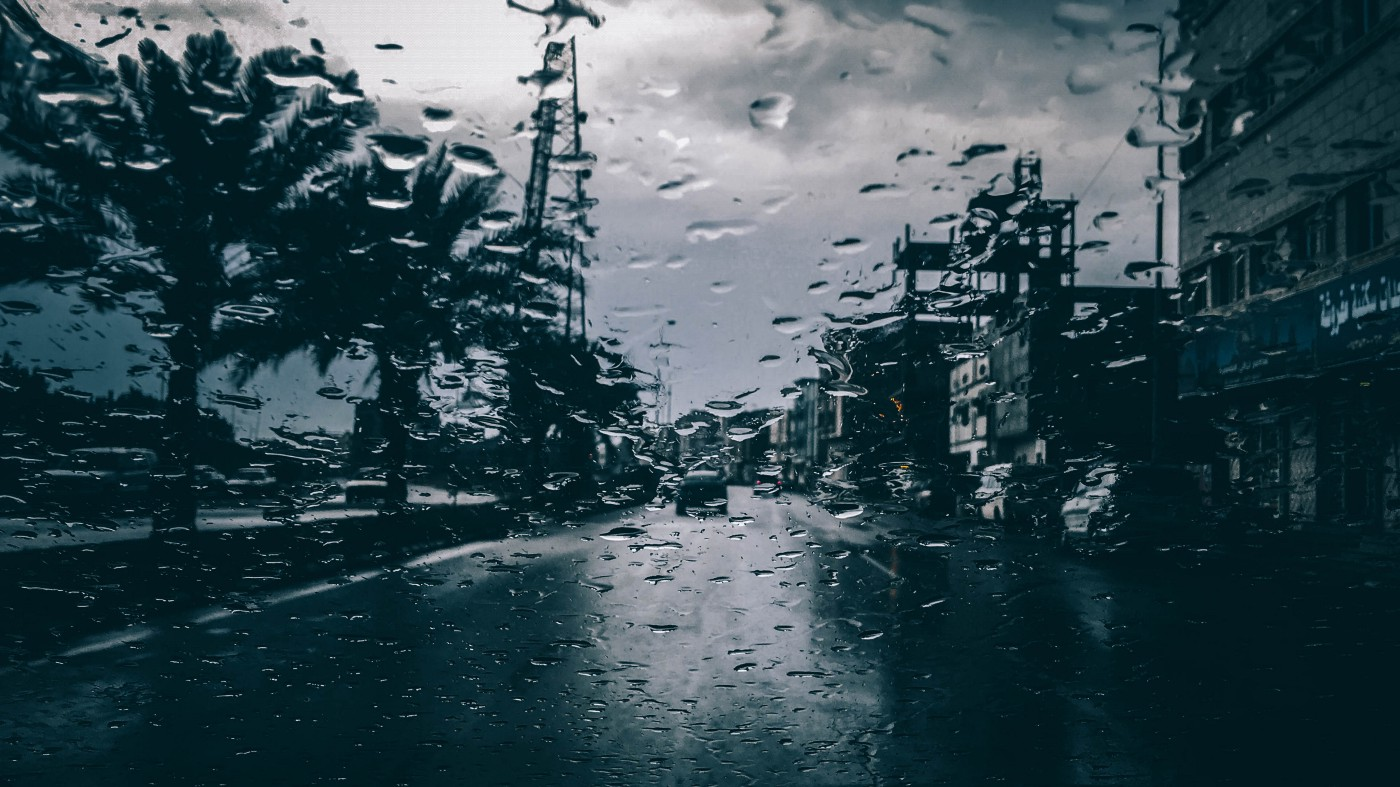 View of road through the wet windshield of a car on a rainy day with dark clouds in the sky, damp dark road below and trees lining one side of the road and buildings the other.