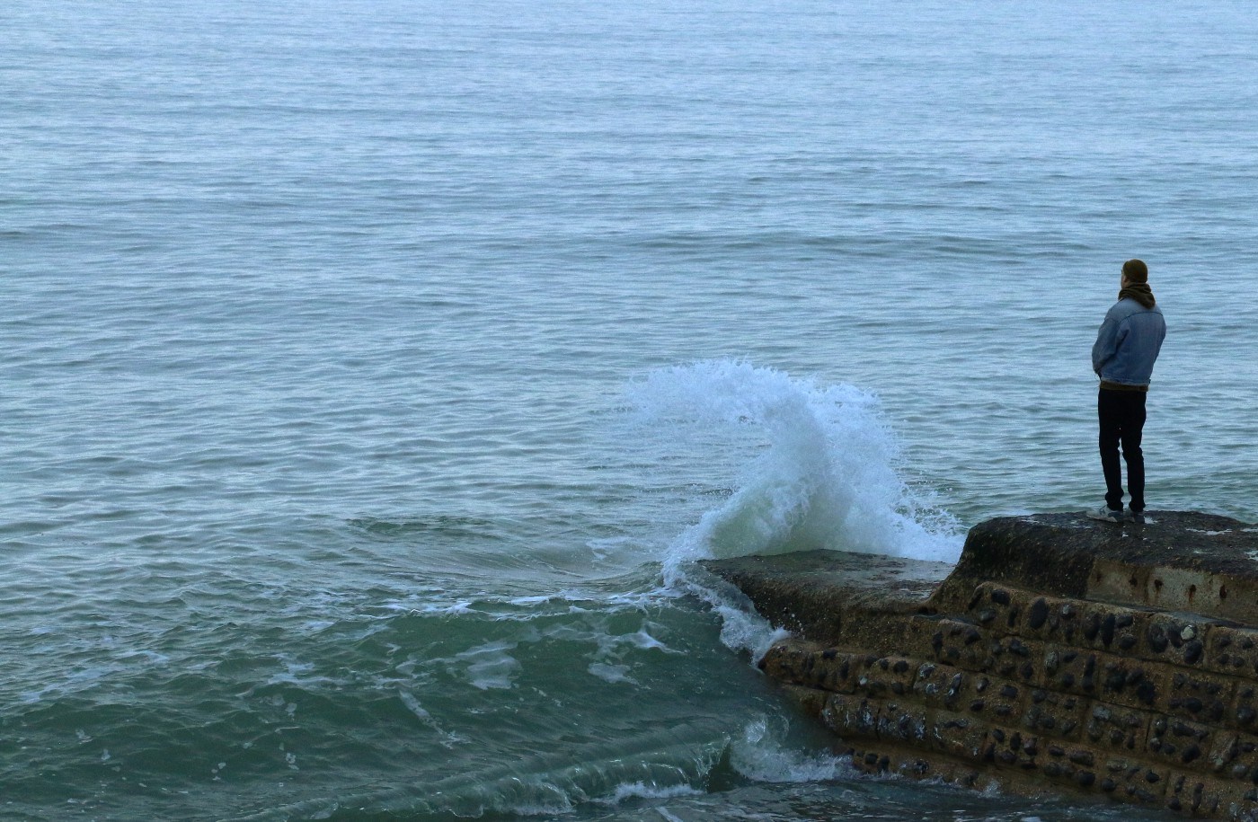 Person standing on a rock jetty peering out into to rough sea.