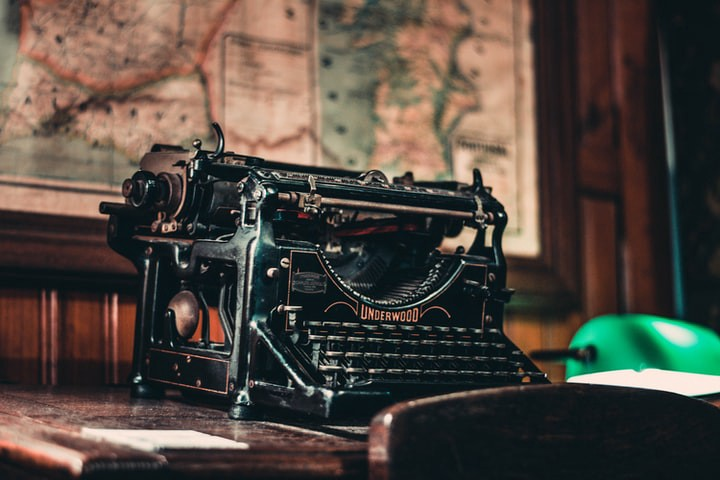 A gorgeous, antique black typewriter with a blank sheet of paper lying next to it, on a wooden desk.