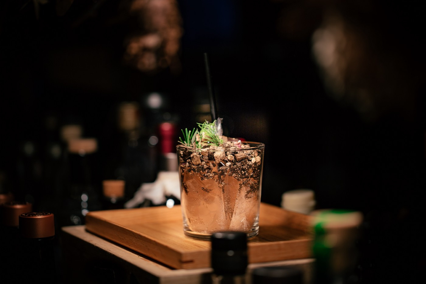 A mixed drink bubbling with a light green garnish in golden liquid and light—almost making it glow—sitting on a golden wooden board, elevated on a bartender's counter but all else is dark around it except the silhouettes and shadows of liquor bottles.
