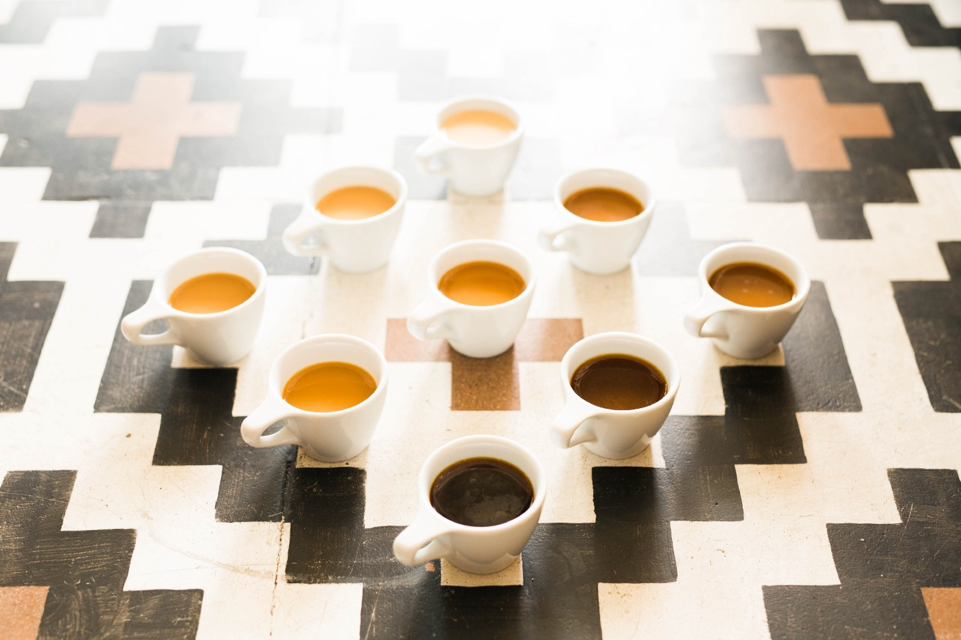 Lots and lots and lots up cups of coffee organized by the shade of the brew foam from light to dark, organized in a diamond.