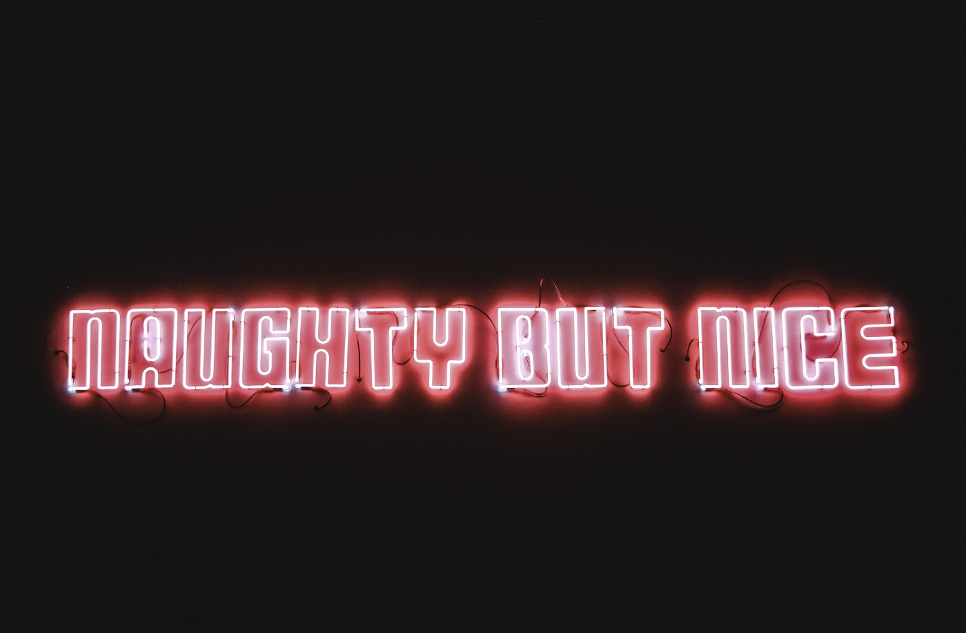 'NAUGHTY BUT NICE' in red and white neon lights