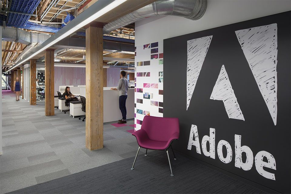 Modern, open floor plan office with exposed ceilings, raw wooden beams, and Adobe branding painted on a brick wall. Picture of the Adobe offices.