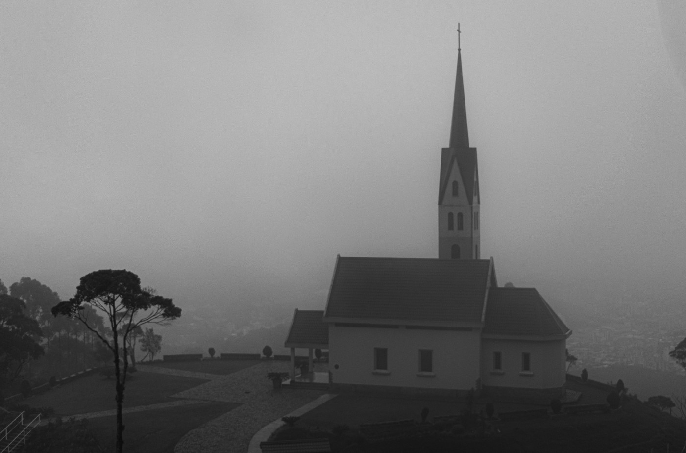 A photo of a church on a hill in black in white.