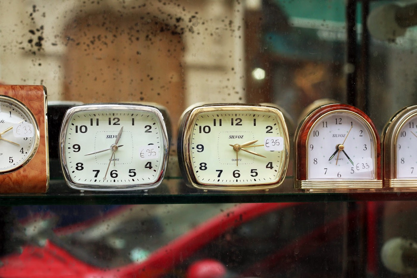 Five clocks with different times lined up next to each other on a shelf