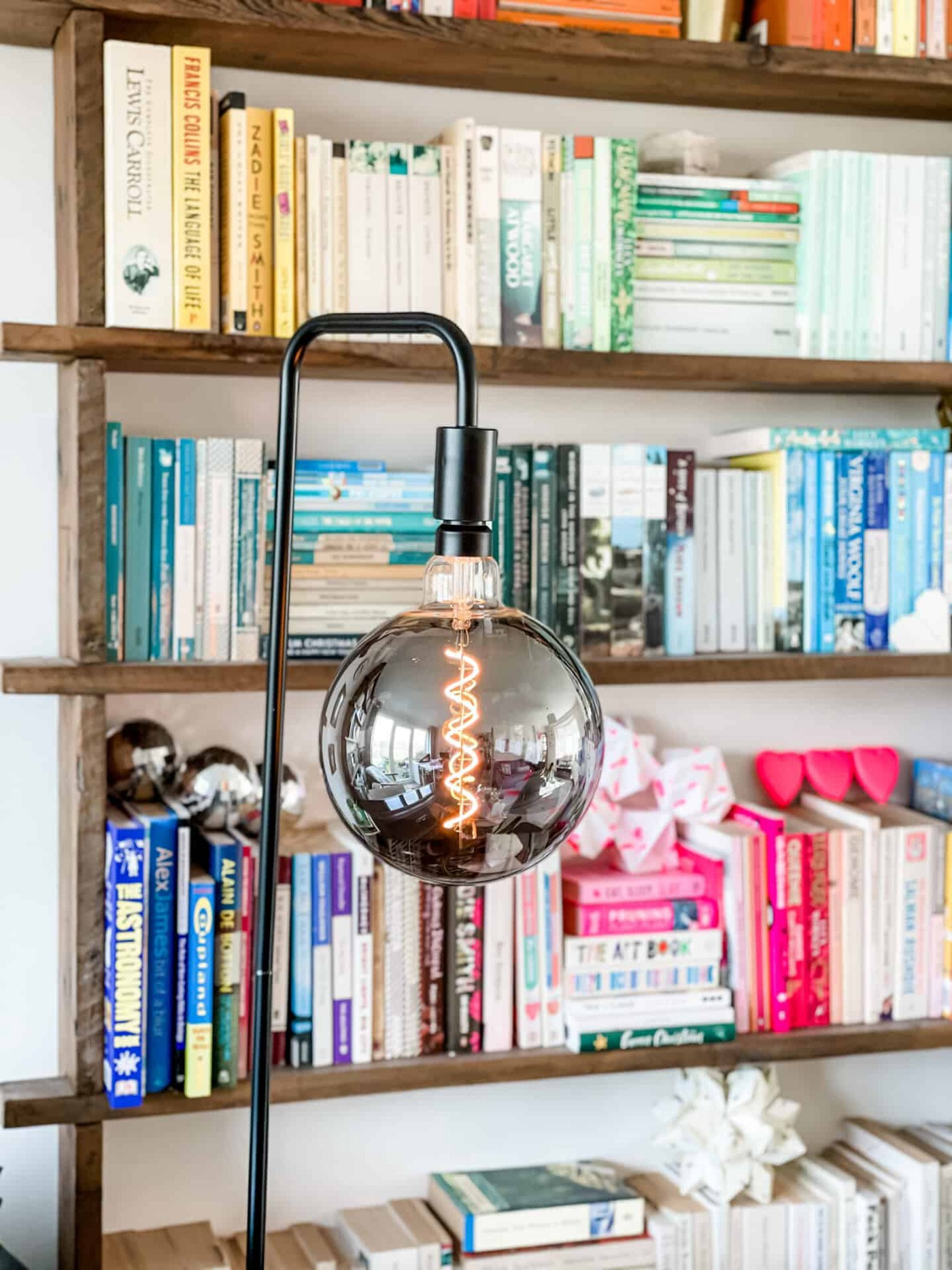 Giant LED bulb in a black industrial floor lamp in front of colour coded bookshelves