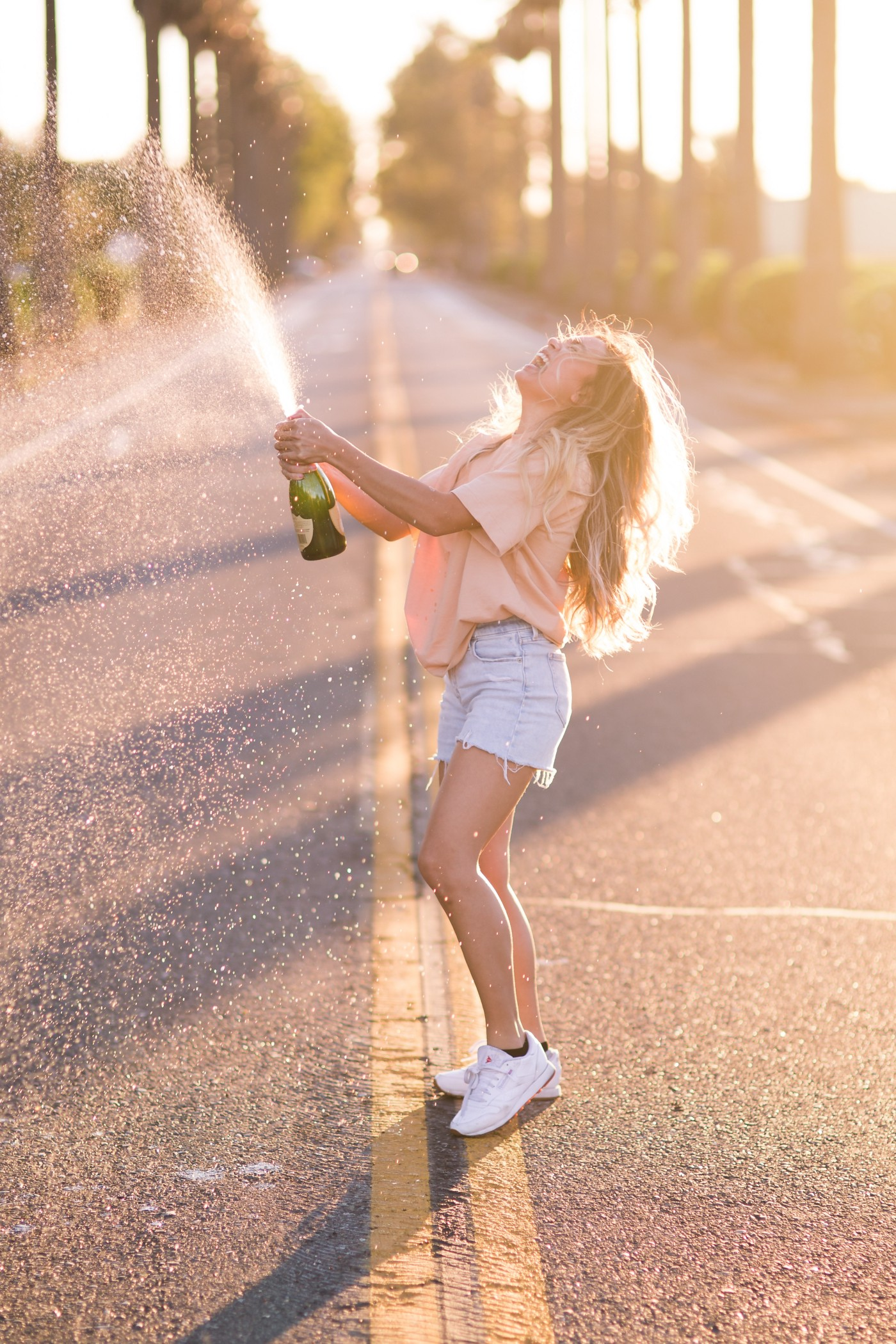 On a sunshiny day in the middle of a road a young wholesome woman in cut off shorts sprays a bottle of champagne in triumphant happiness.