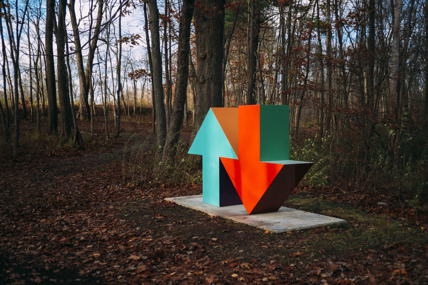 A sculpture of two arrows in woodland