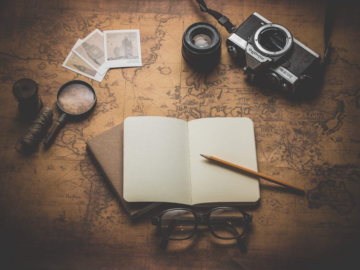A notebook, a camera, some cards, a loop, and a pen on a table