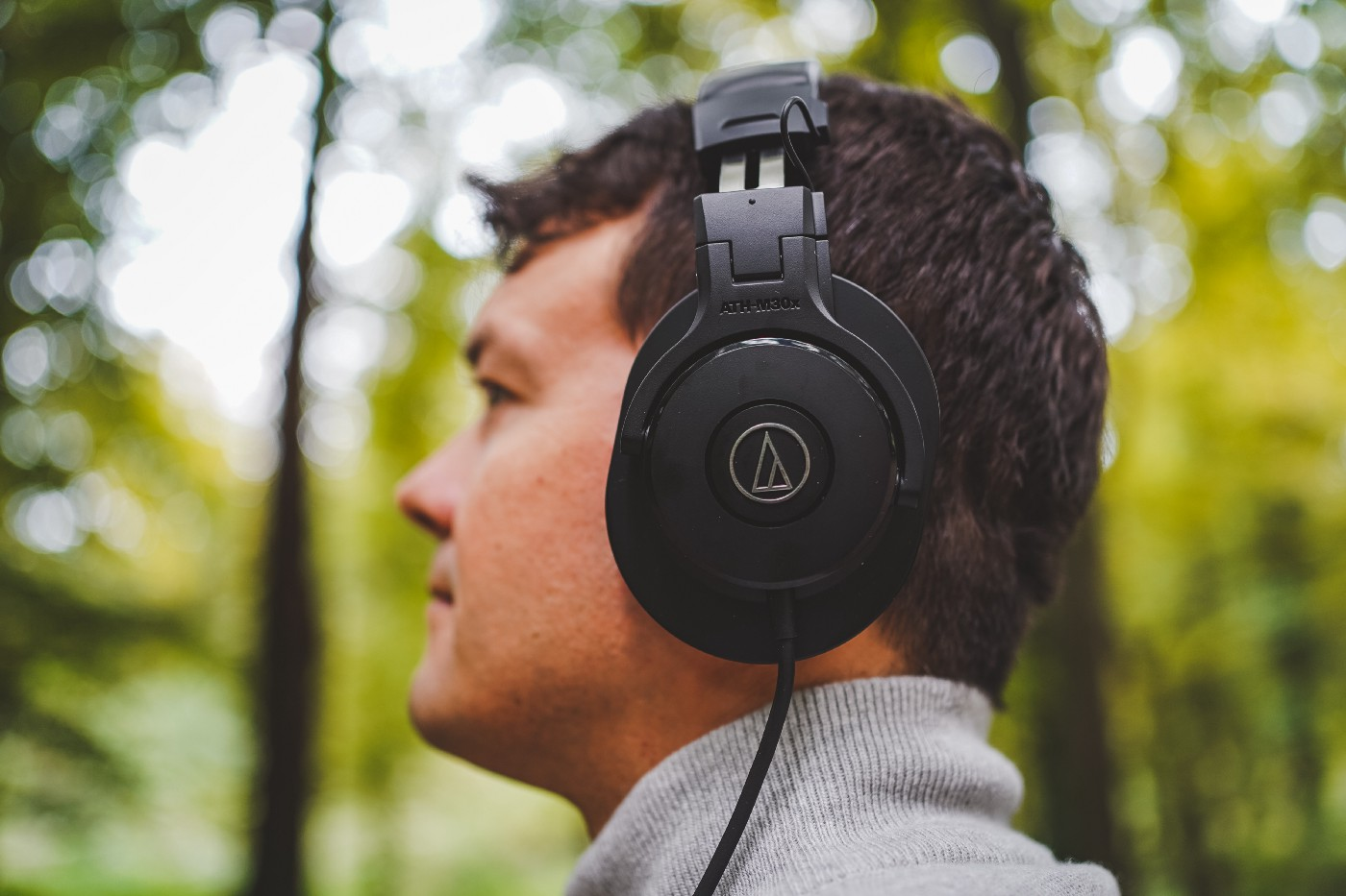 Man wearing headphones, in the woods