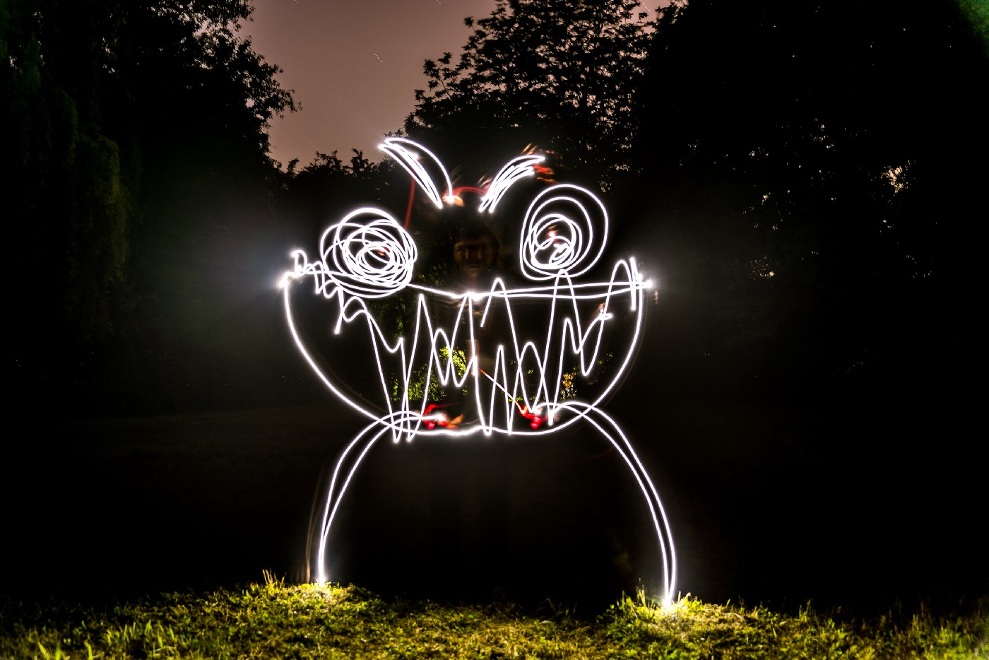 picture of a grinning alien drawn with a flashlight at dusk