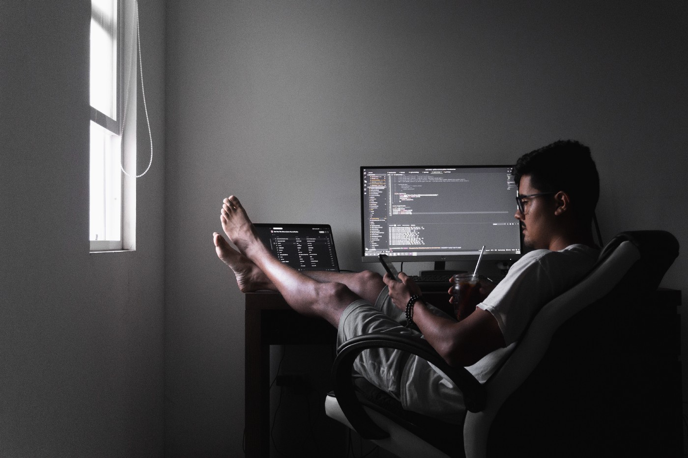 Guy sitting in his shorts at his computer screen; The Rhetoric of Hustle Culture