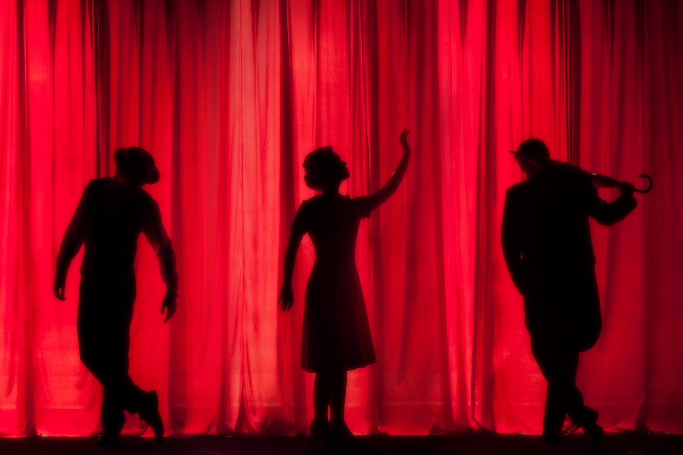 Three performers silhouetted against a red velvet curtain.