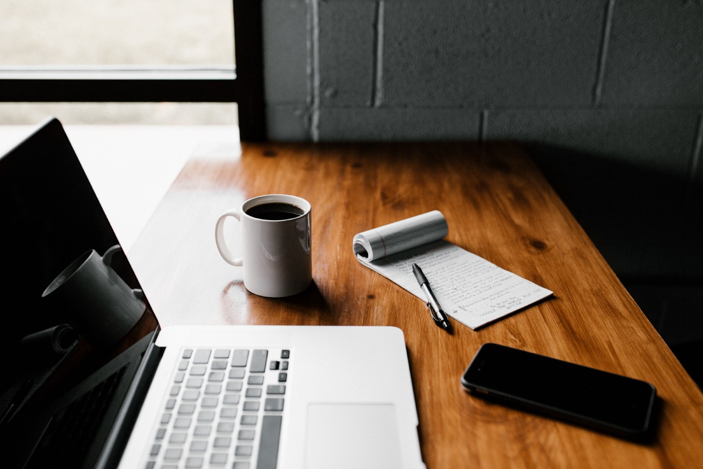 A clean hardwood workspace features an open laptop, coffee, phone, and to-do list with a pen resting neatly beside it.
