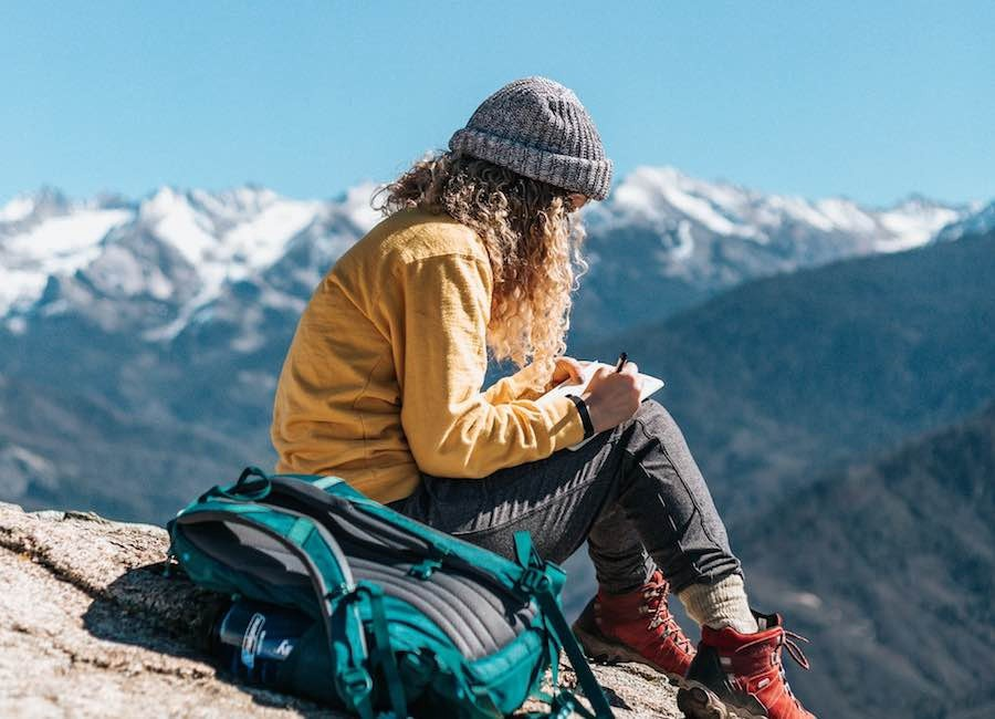 Young woman sitting on mountain and writing in notebook