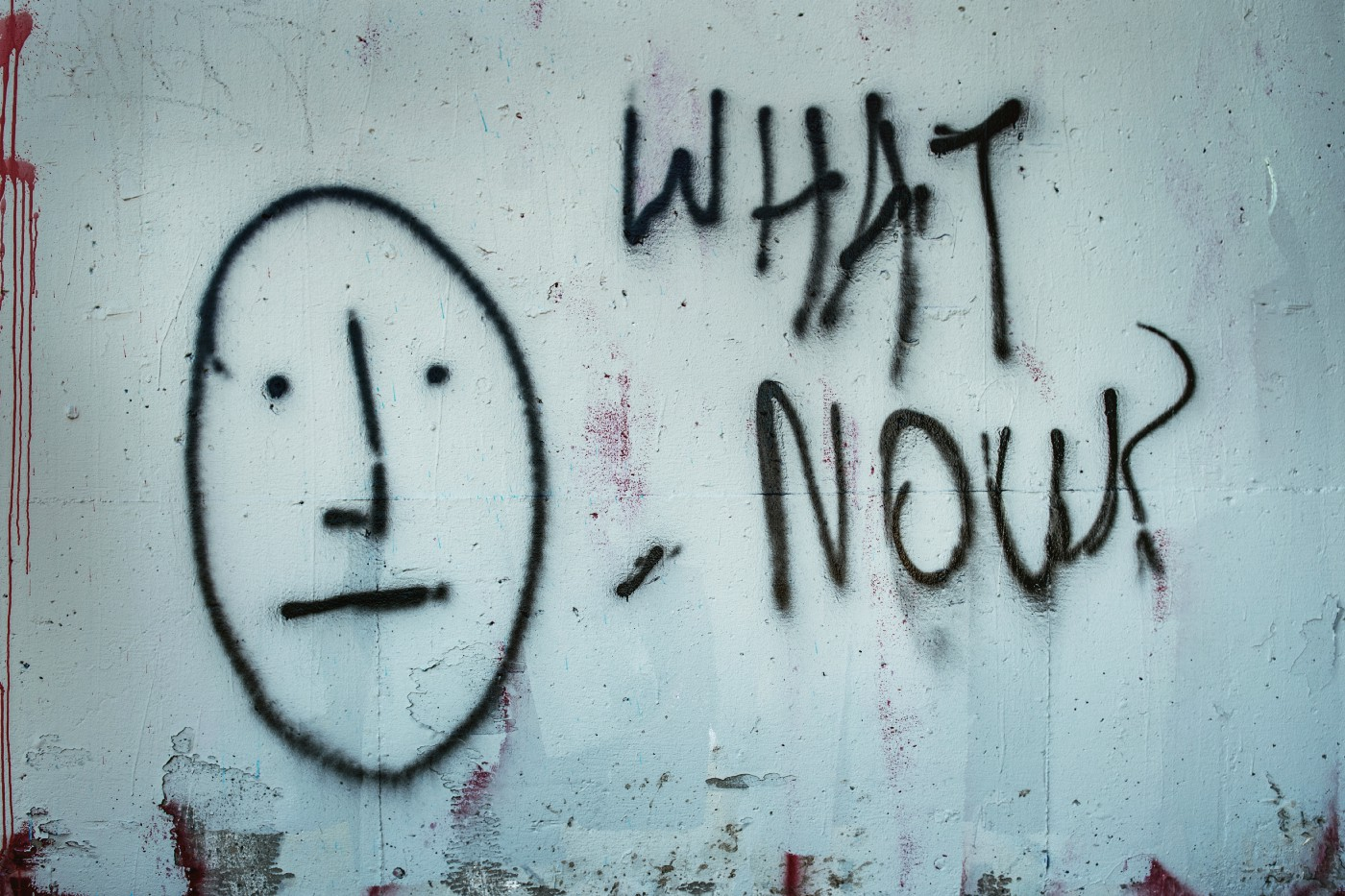 Street art depitcting an anxious face with the words 'what now?'