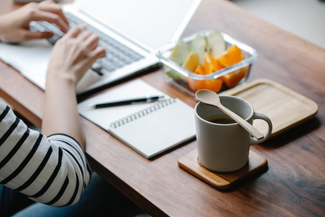 A woman is typing on her laptop. A notebook, cup of coffee, and fruit sit closely on her desk. #freelancing #writing #workfromhome #writer #wfh