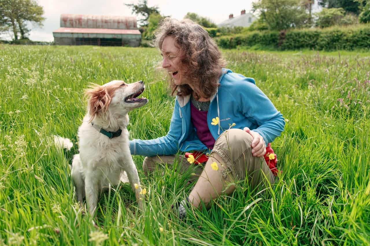 Woman and dog laughing together in a field