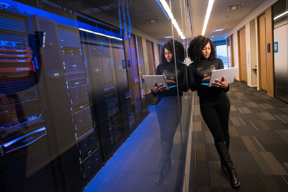 Woman standing by computer servers