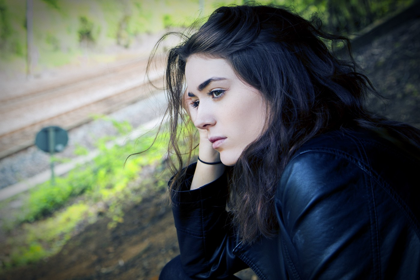 A young women staring into the distance with jet black hair thinking