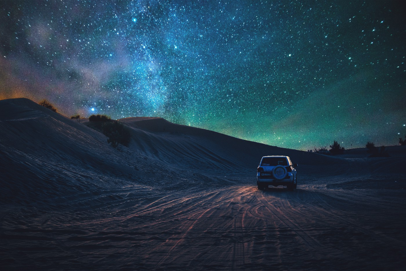 car driving at night under sky lit up by the Aurora Borealis